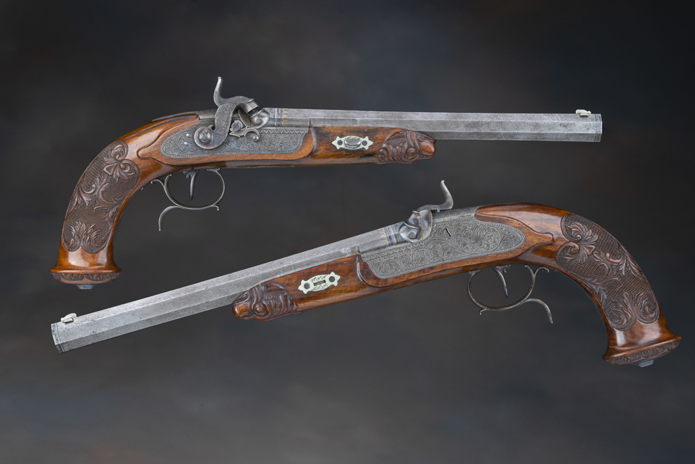 """Cased Pair of G. & W. Pistor Percussion Target Pistols.  Brothers Georg and Wilhelm Pistor were part of the Pistor family of gun makers in the 1830s to 1850s in Schmalkalden, Germany.  The Damascus barrels are each signed """"G. & W. PISTOR IN SCHMALKALDEN"""" in gold inlay and have eight-groove rifling, dove tailed German silver blade front sights, golden loop patterns at the breech, and silver bands at the muzzle and breech.  The bottom of the barrels and breech plugs have """"11981/G&WP"""" and the lower right flats have rampant lion and """"NR"""" markings.  The standing breeches have adjustable notch rear sights and are gold inlaid with """"1"""" and """"2"""" respectively.  The locks are discreetly signed """"G. & W. PISTOR"""" at the front and have rotating hammer stalls, and the side plates have """"IN SCHMALKALDEN.""""  The pistols also have adjustable single set triggers and spurred trigger guards.  In addition to the Damascus pattern barrels, the other various components have scroll engraving and detailed borders, and there is also a stand of arms design on the trigger guard.  The stocks have finely carved dog's heads at the forend tips, checkering with scroll carved accents on the wrist, floral carving around the edge of the pommels, and steel caps. They come in very attractive figured hardwood case with """"G . & W. Pistor / in / Schmalkalden"""" inside the lid and interior closely fitted to the pistols and the set of matching accessories (bullet mold absent), which include rods (tips absent), mallet, cap / ball container, powder flask, screwdriver, nipple wrench, powder measure, patch punch, and rear sight adjustment key.  Fine condition with distinct Damascus patterns, light gray and brown patina, bright gold, some minor spots of oxidation / discoloration, and natural aged patina on the bands on the barrel; 40% original case colors on the lock and furniture, crisp markings and engraving, and generally only minor storage wear.  The stock is very fine aside from a reglued chip on the left by the side"""